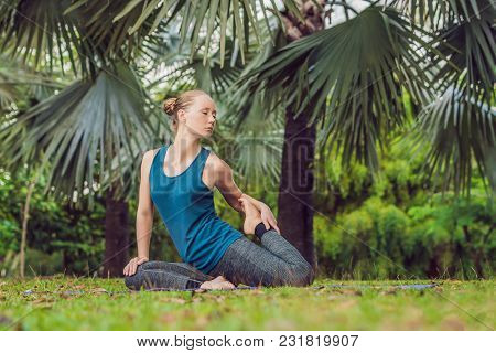 Woman Practicing Yoga In A Tropical Park.