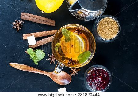 Autumn Warming Tea With Lemon, Mint In A Glass Cup And Raspberry Jam On A Black Background. Copy Spa