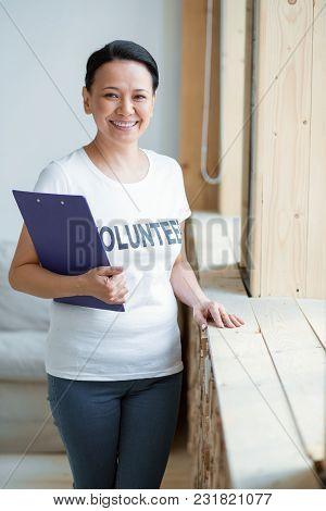 Volunteer Organization. Vigorous Jovial Female Volunteer Holding Clipboard While Staring At Camera A