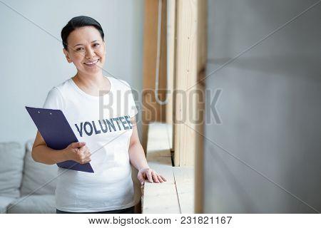 International Volunteering. Enthusiastic Successful Female Volunteer Carrying Clipboard While Starin