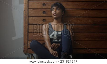 Young Fit And Tone Up Woman Sits Lean On Wooden Wardrobe During Workout Rest In Loft