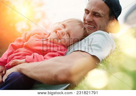 Father Playing With Smiling Daughter In The Park At Sunny Day, Intentional Sun Glare And Lens Flares