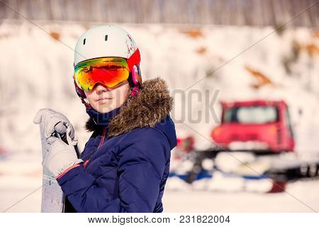 Portrait Of Female Athlete In Mask And Helmet On Blurred Snowy Day Background. Toned Photo