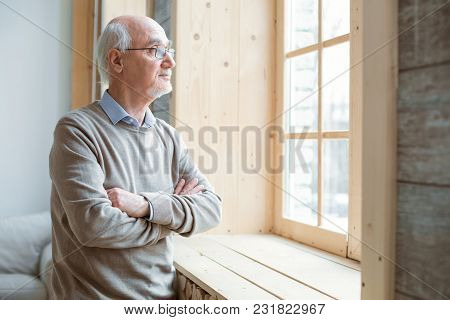 Pensive Mood. Thoughtful Attractive Senior Man Gazing Through Window While Crossing Hands And Stayin
