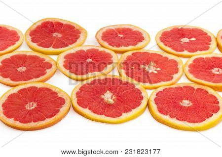 Round Slices Of The Ripe Red Grapefruits With Peel On A White Background At Shallow Depth Of Field