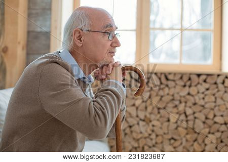 Sweet Dreams. Attractive Pensive Senior Man Sitting In Profile While Leaning On Cane And Wearing Gla