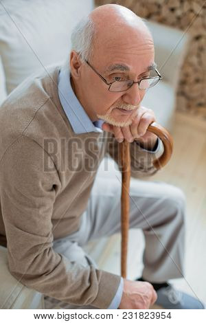Thoughtful Mood. Top View Of Experienced Successful Senior Man Thinking While Leaning On Cane And Si