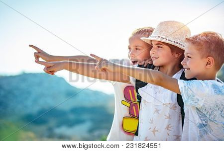Portrait of a three happy friends outdoors, kids with wonder looking at the view, with excitement enjoying amazing mountains, best friends with pleasure spending summer holidays together