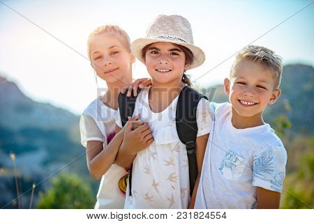Portrait of a three happy friends outdoors, siblings with pleasure traveling together, having fun in summer camp, best friends forever
