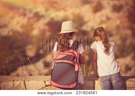 Summer camp adventures, two little girls best friends enjoying mountains hike, schoolchildren on outdoor tour, happy summer holidays in the camp