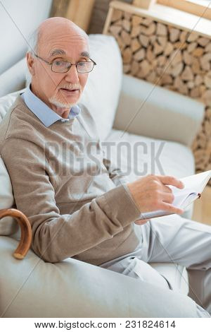 Ordinary Day. Top View Of Smart Intelligent Senior Man Sitting On Sofa While Holding Book And Wearin