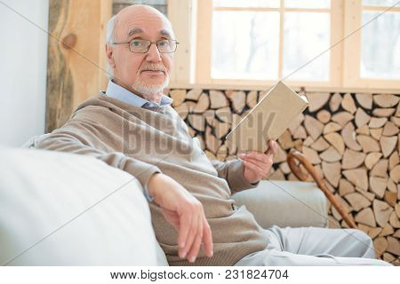 My Routine. Positive Musing Senior Man Sitting On Sofa While Carrying Book And Gazing At Camera