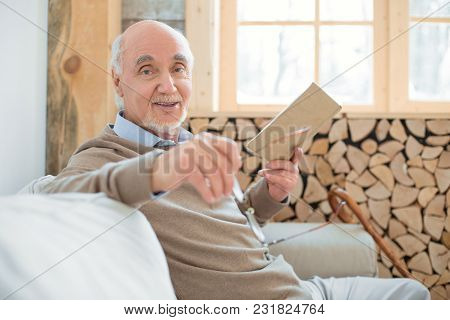 Exercise For Brain. Joyful Merry Senior Man Sitting On Couch While Holding Glasses And Reading Book