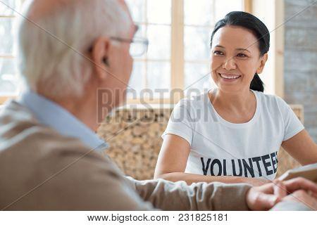 Welfare Volunteering. Cheerful Jovial Volunteer Smiling While Speaking To Senior Man And Looking At