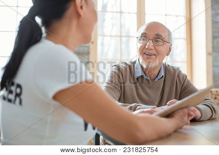 Twisted Plot. Cheerful Merry Senior Man Laughing While Listening To Volunteer And Sitting On Blurred