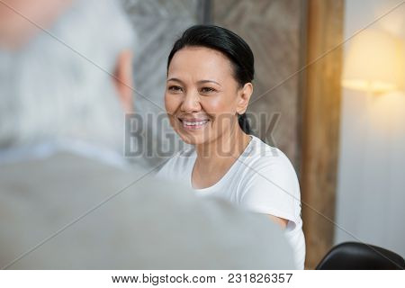 Helpful Doing. Happy Merry Volunteer Grinning While Posing On Blurred Background And Listening