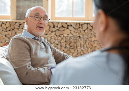 Health Issue. Experienced Nice Senior Man Sitting While Wearing Glasses And Talking To Doctor