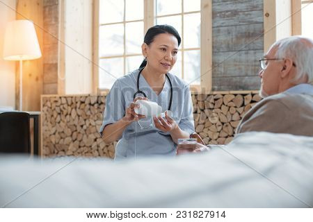 Help Your Body. Appealing Asian Doctor Holding Bottle Filled With Pills While Looking At Senior Man