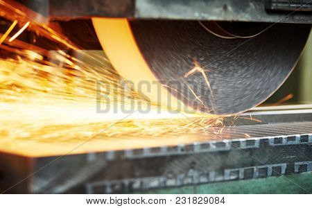 industrial grinding. finishing metal surface on horizontal grinder machine