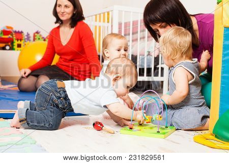 Four Moms With Children Sitting In Playroom