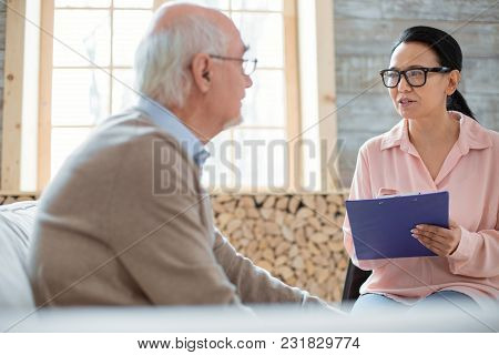 Detailed Notes. Experienced Confident Caregiver Holding Clipboard While Wearing Glasses And Helping