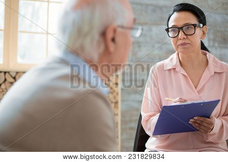 Daily Life. Earnest Concentrated Caregiver Carrying Clipboard While Wearing Glasses And Listening To