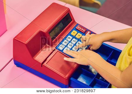 The Boy Plays With The Children's Cash Register