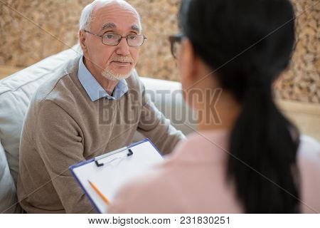 First Meeting. Pleasant Experienced Senior Man Posing On Sofa While Staring At Caregiver And Communi