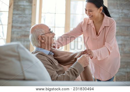 First Conversation. Attentive Kind Caregiver Standing While Smiling And Giving Blanket To Senior Man