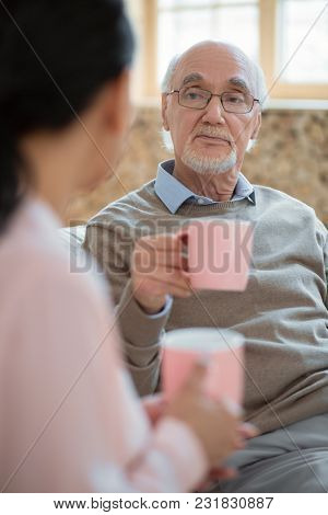 Pink Mug. Positive Pleased Senior Man Communicating With Caregiver While Drinking Tea And Carrying M