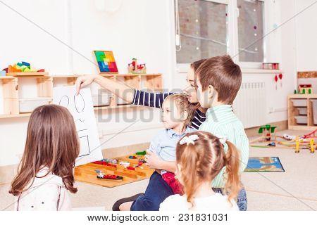 Beautiful Young Teacher Showing Figures Preschoolers, Children Sit In A Circle