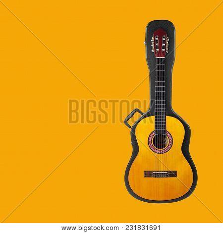 Musical Instrument - Acoustic Classic Guitar From Above On A Hard Case On A Yellow Background.