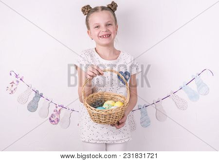 Congratulations On Happy Easter: The Girl Is Holding A Basket With Painted Eggs By The White Wall. P