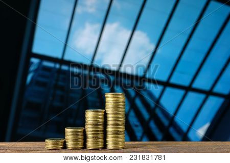 Step Of Coin Stack On Top Wooden Working Table With City City And Office Building Background, Busine