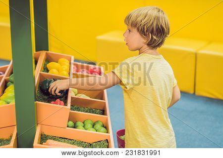 A Boy Buys Toy Vegetables In A Toy Supermarket.