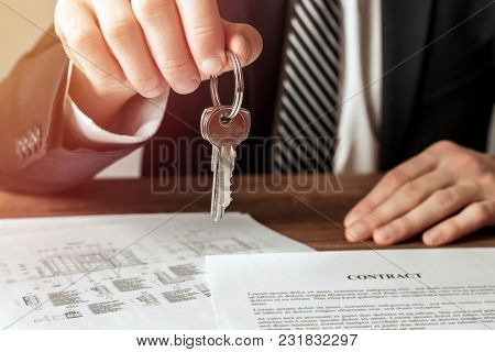 Real Estate Agent Giving House Key To His Client After Signing Contract Agreement. Real Estate Conce