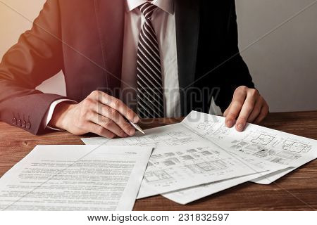 Architect Man Holding A Pen With Blueprints For An Architectural Plan, An Engineer Sketching A Const
