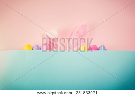 Easter Rabbit Ears And Row Of Easter Colored Eggs On Pink And Blue Background With Copy Space, Retro