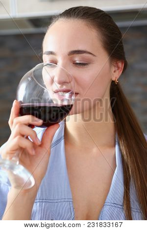 Beautiful Smiling Brunette Woman Hold In Arms Glass Of Red Wine At Kitchen Table Portrait. Vine Cabe