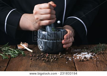 Woman Chef Pounding Spices And Herbs In Mortar For Food Cooking On A Black Background.
