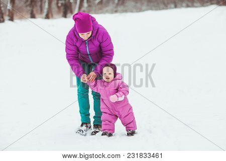 Mom With A Little Daughter Dressed In Warm Clothes, Walking In The Winter Park