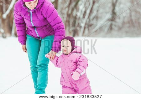 Mother And Daugher Are Playing On Winter Walk In The Park