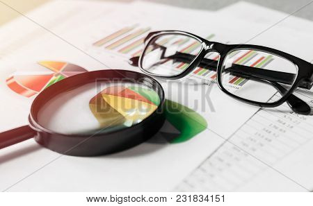 Business Reports And A Magnifying Glass With Glasses On Table Office. Concept Of Data Analysis, Inve