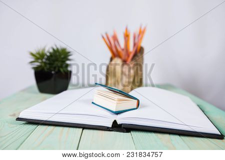 Set Of Pencils And Pile Of Various Books On Wooden Background. With Copy Space For Your Text