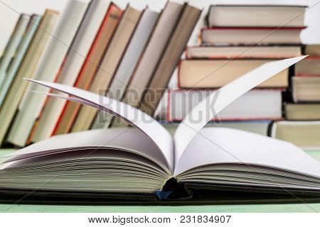 Open Book And Pile Of Various Books On Wooden Background. With Copy Space For Your Text