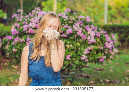 Pollen Allergy Concept. Young Woman Is Going To Sneeze. Flowering Trees In Background.