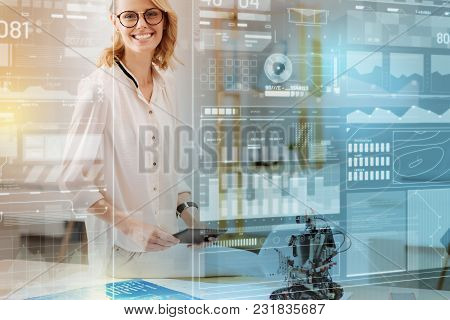 Cheerful Smile. Beautiful Young Optimistic Engineer Sitting On The Table With A Modern Tablet In Her