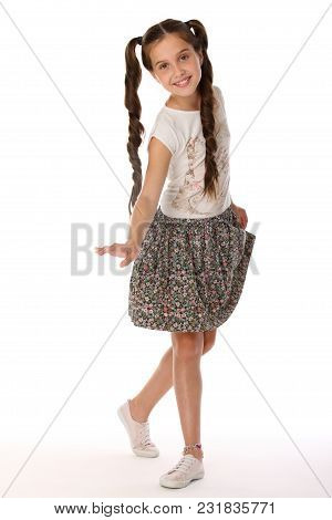 A Little Girl 12 Years Old Posing In Summer Clothes. Charming Pretty Slender Young Teenager Is In A