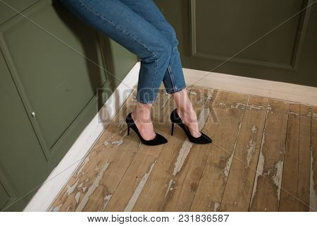 Legs Of A Girl In Black High-heeled Shoes And Blue Jeans