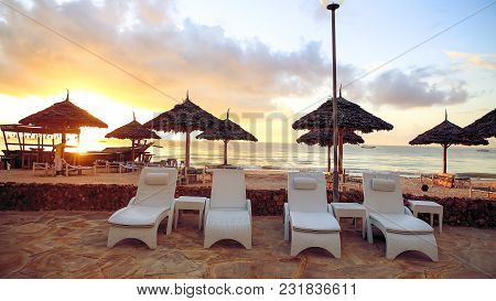 Beach With Sun Loungers And A Place For Rest At Sunset.
